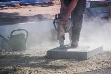 Construction worker using tool while dust blows into air - Construction dust