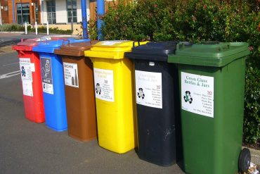 Six recycle bins in front of building - Construction recycling