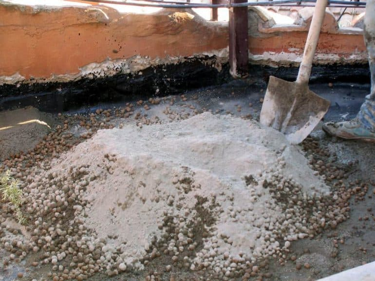 Builders mixing pumice pebbles with concrete - Building with pumice