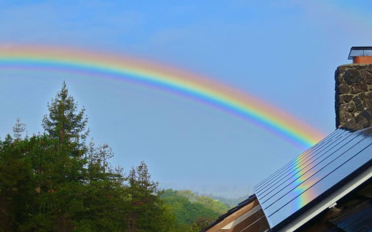 Solar panels on house with rainbow