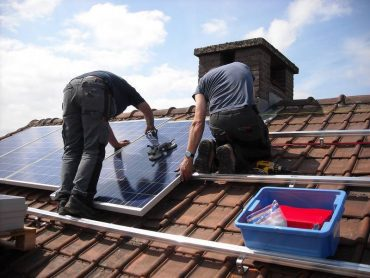Two people installing solar panels on roof of house - Solar rooftop DIY
