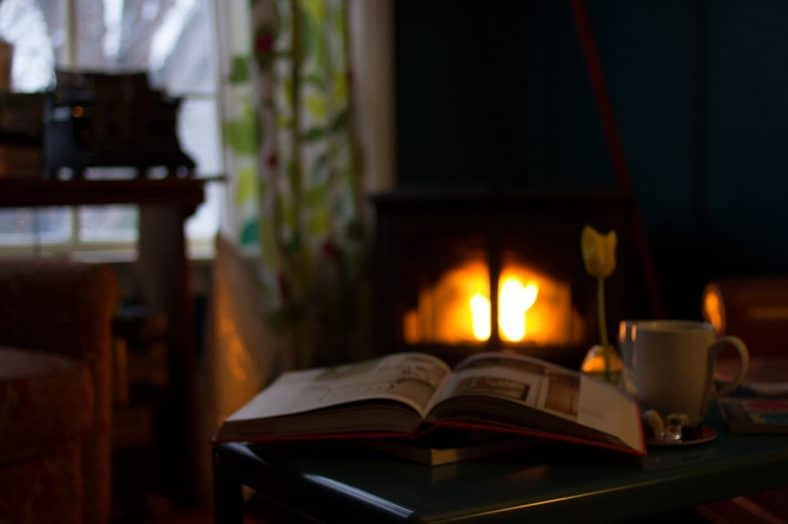 Book on table in front of fireplace beside window - 6 green strategies for reducing home heating costs