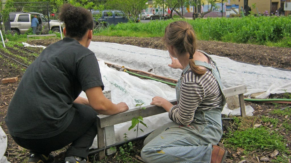 Two female farm workers at East New York Farms surveying layout - Outdoor classroom
