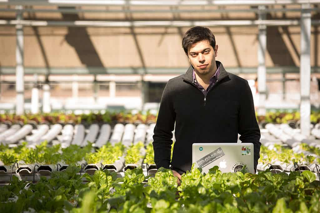 Founder Mohamed Hage in LUFA farms rooftop greenhouse with laptop