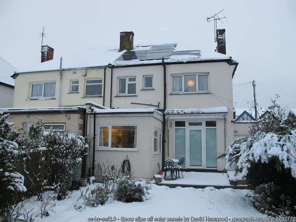Snow sliding off a house's solar panels - 8 types of weather that can affect solar panel efficiency