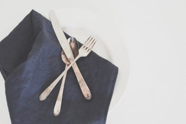 Silver metal cutlery and a navy blue napkin - Ditch the single-use plastics