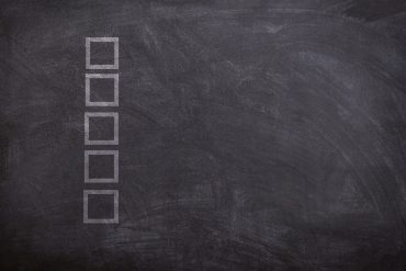 Check boxes on chalkboard - Green home buying checklist