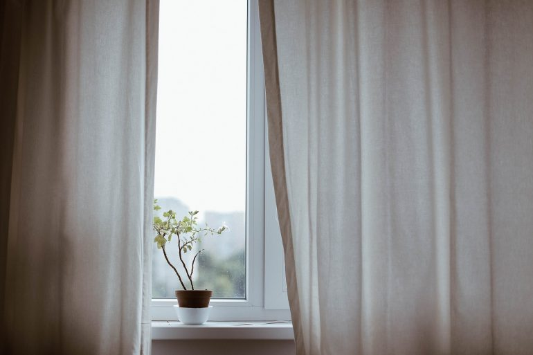 Window with curtains and small plant - 3 do-it-yourself projects for an energy efficient home
