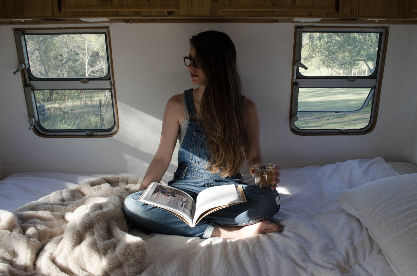Woman sitting on bed inside tiny home - The tiny home trend