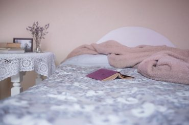 Bed with blanket and book via Pixabay