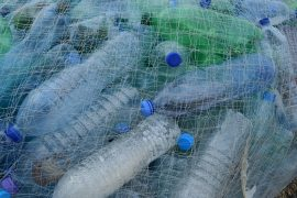 Plastic bottles in fishing net. Photo via Pixabay.