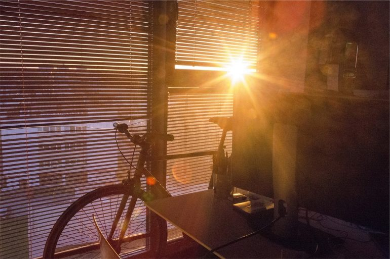 Window blinds with bike in front. Photo via Pixabay.