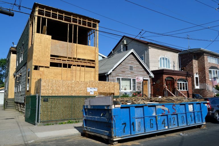Dumpster in front of home under construction. Photo from Pixabay.