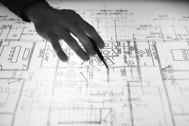 Black and white image of architect with pen. Photo via Pexels.