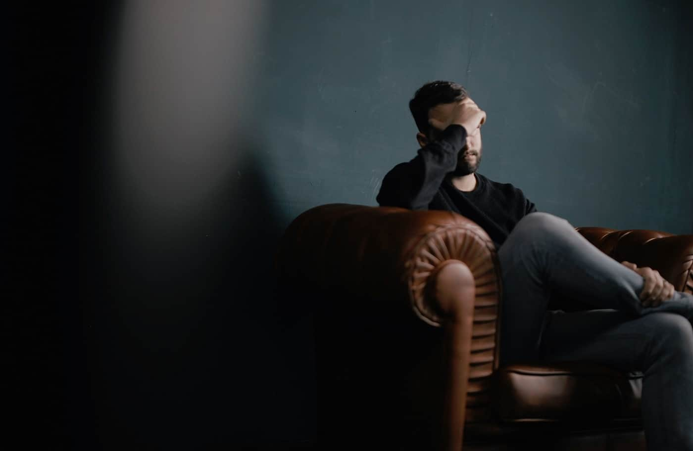 Man sitting on couch with headache. Image from Pixabay.