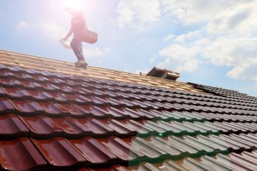 Roofer working on roof. Image from Shutterstock.