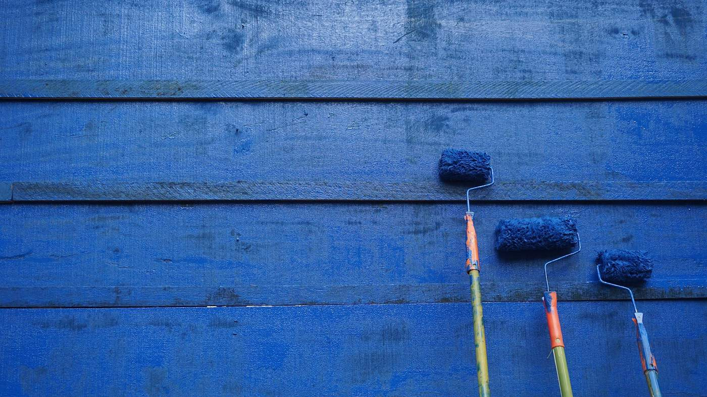 Blue house with three paint rollers leaning against it. Photo from Pixabay.