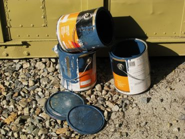 Three paint cans sitting on ground