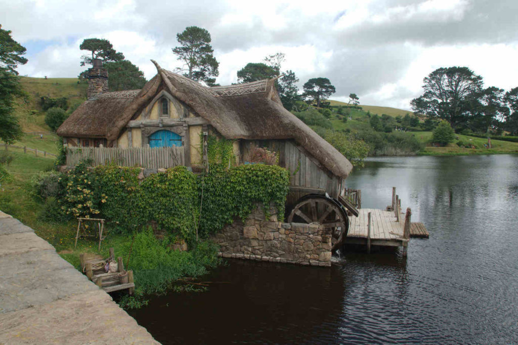 thatched roof house with watermill - the basics of living off the grid