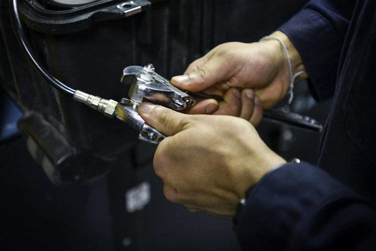 person checking air compressor gauge - choosing a green air compressor